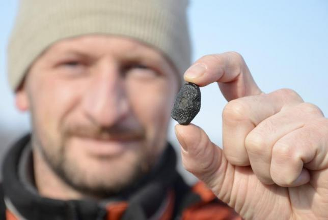 A local resident shows a fragment thought to be part of a meteorite collected in a snow covered field in the Yetkulski region outside the Urals city of Chelyabinsk February 24, 2013. REUTERS/Andrei Romanov