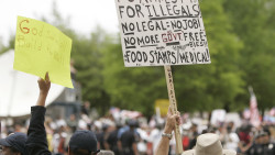 ORG XMIT: TXMF107 Anti-immigration demonstrators hold signs at an immigration rally in Dallas on Saturday, May 1, 2010. Large crowds were expected in Dallas after a new Arizona law passed requiring authorities to question people about their immigration status if they are suspected of being in the country illegally. (AP Photo/Mike Fuentes)